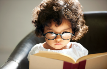 Kid reading in glasses